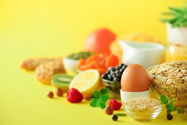 Petit déjeuner végétarien. œuf à la coque, flocons d'avoine, noix, fruits, baies, lait, yaourt, orange, banane, pêche