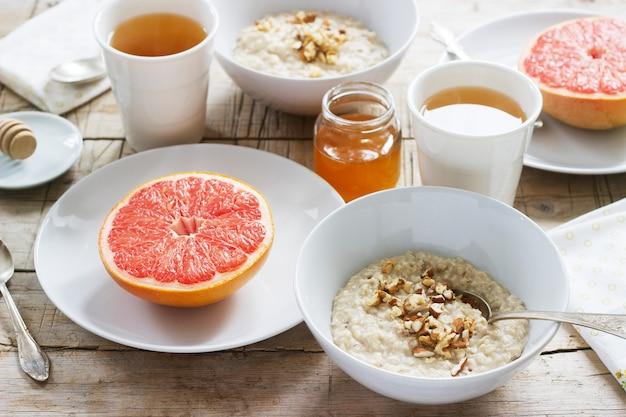 Petit-déjeuner végétarien pour deux composé de flocons d'avoine, de pamplemousses cuits et de thé