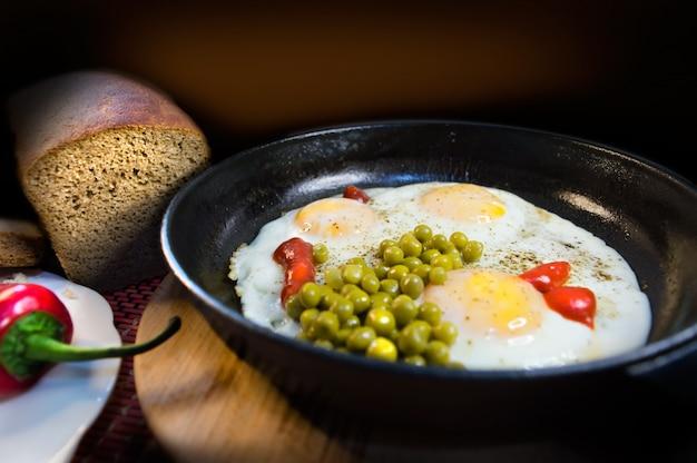 Petit-déjeuner vintage sur une poêle en fonte avec trois œufs, des pois, une sauce, du pain et du poivre sur un fond sombre.