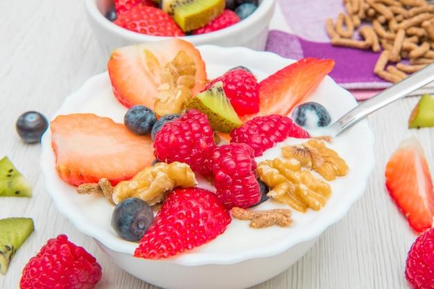 Petit-déjeuner avec yaourt, fraise, framboise et céréales