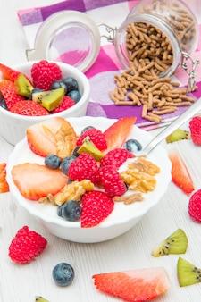 Petit-déjeuner avec yaourts, fruits et céréales