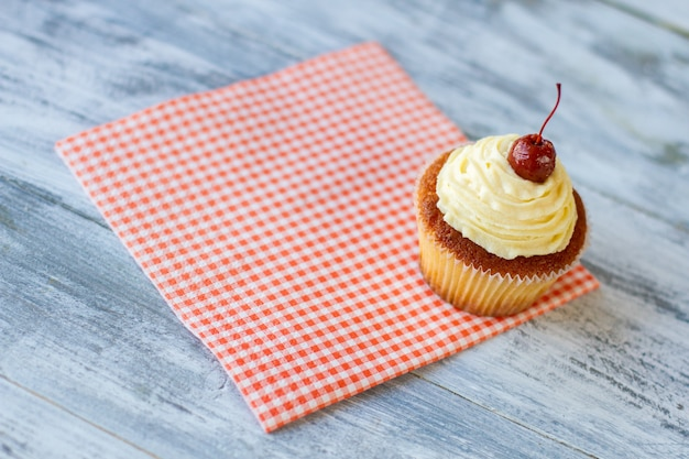 Petit dessert sur pâte de serviette avec glaçage et cerise essayez un nouveau dessert au café frais et appétissant cu...
