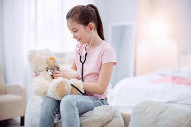 Petit docteur. enthousiaste jolly jolie fille audition ours en peluche tout en posant sur fond flou et souriant