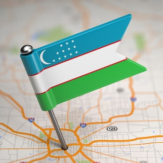 Petit drapeau de l'ouzbékistan sur un fond de carte avec mise au point sélective.