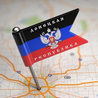 Petit drapeau de la république populaire de donetsk - collé dans l'arrière-plan de la carte avec mise au point sélective.