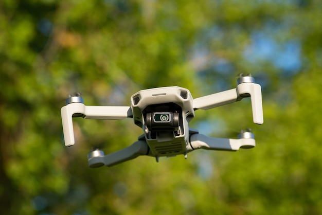 Petit drone avec caméra en l'air avec des arbres au