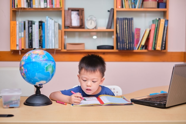 Petit écolier asiatique à l'aide d'un ordinateur portable pour étudier les devoirs au cours de sa leçon en ligne à la maison