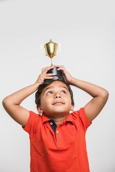 Petit écolier asiatique indien tenant un trophée ou une coupe gagnante contre un tableau blanc ou vert