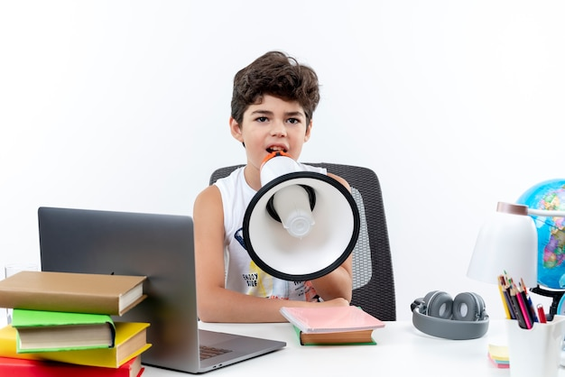 Petit écolier assis au bureau avec des outils scolaires parle sur haut-parleur