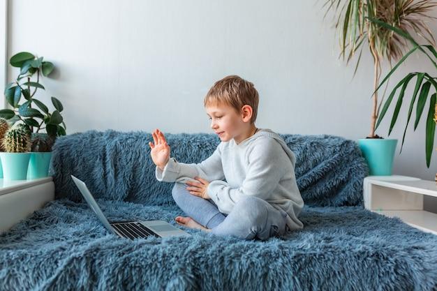 Petit écolier ayant un appel vidéo, cours en ligne sur ordinateur portable e-learning, étude à distance, concept de communication à distance