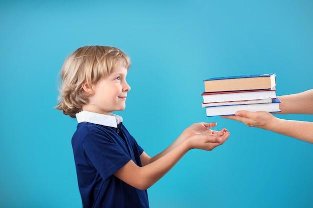 Petit écolier blonde heureuse prenant des livres dans la bibliothèque
