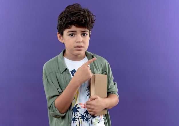 Petit écolier concerné tenant un livre et des points sur le côté isolé sur un mur violet avec copie espace