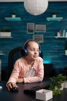 Petit écolier avec des écouteurs s'occupant de la leçon en classe de littérature en ligne