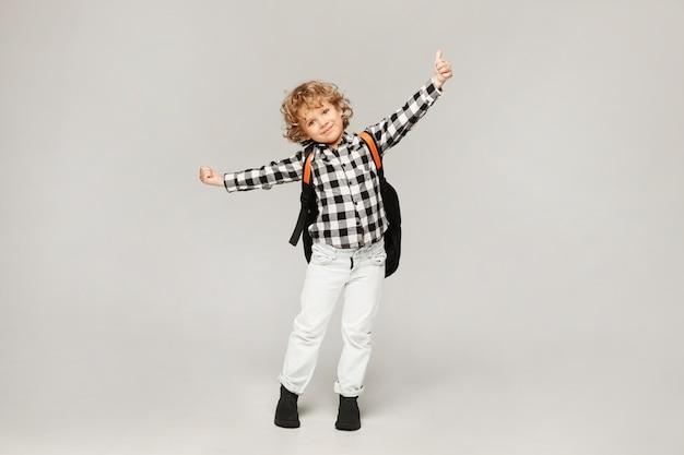 Un petit écolier est heureux de commencer l'année scolaire. enfant heureux avec un sac à dos posant, isolé.