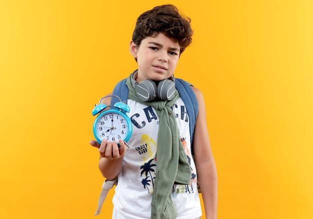 Petit écolier insatisfait portant sac à dos et écouteurs tenant un réveil isolé sur jaune