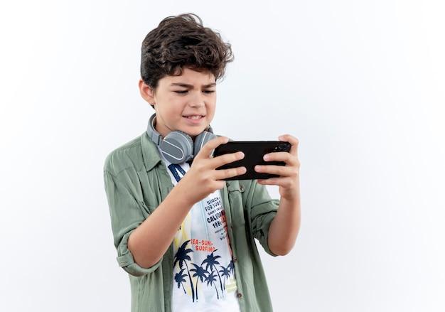 Petit écolier portant des écouteurs et jouant au téléphone isolé sur blanc