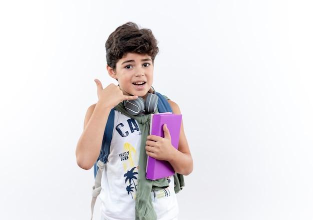 Petit écolier portant un sac à dos et des écouteurs tenant un livre et montrant un geste d'appel téléphonique