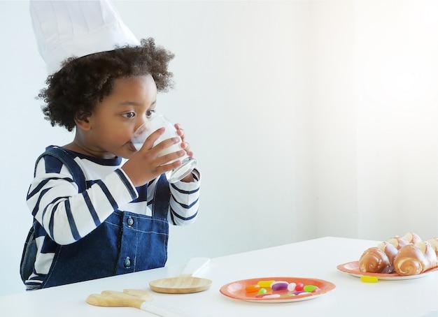 Petit enfant africain mignon portant un chapeau de chef boit du lait