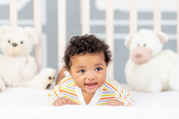 Petit enfant afro-américain couché dans son lit dans des vêtements orange avec des ours mous
