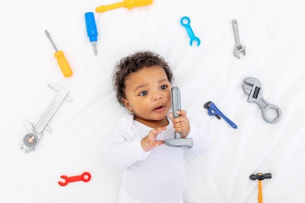 Petit enfant afro-américain avec des outils de construction allongé sur un lit blanc, concept de construction et de réparation