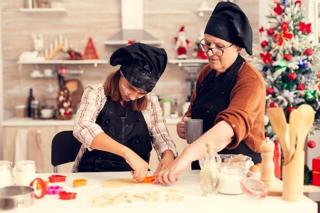 Petit-enfant à l'aide d'un coupe-pâte le jour de noël