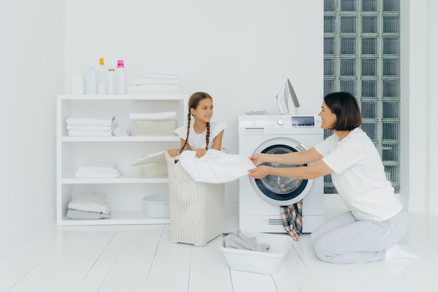 Petit enfant aide maman à laver, s'assoit dans le panier avec le linge