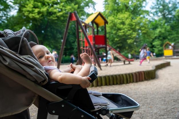 Un petit enfant sur l'aire de jeux dans un landau