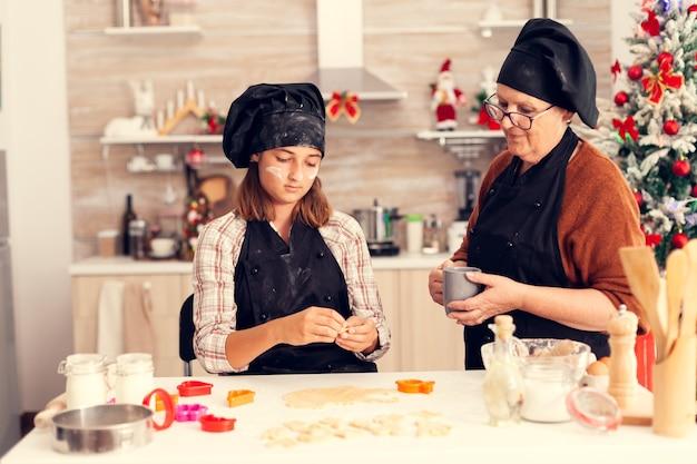 Petit-enfant apprenant à faire de la pâte le jour de noël