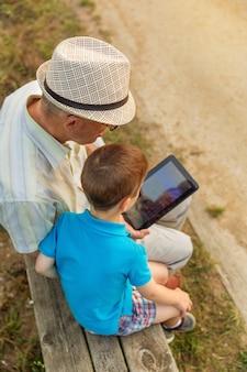 Petit-enfant apprenant à son grand-père à utiliser une tablette électronique sur un banc de parc. concept de valeurs de génération.