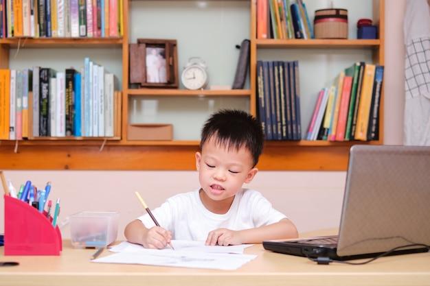 Petit enfant asiatique dessinant pendant sa leçon en ligne à la maison, à distance, concept homeschooling