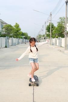 Petit enfant asiatique de jeune fille patinant sur la planche à roulettes à la rue
