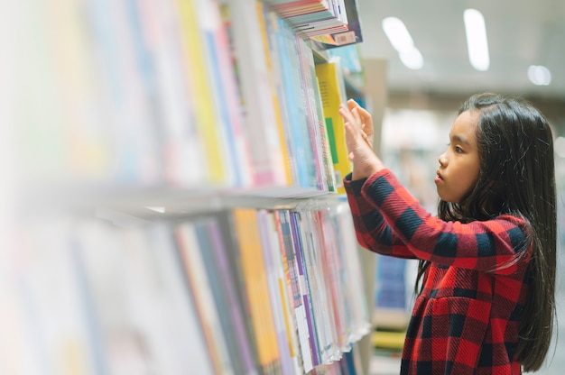 Petit enfant asiatique, ramasser des livres de l'étagère