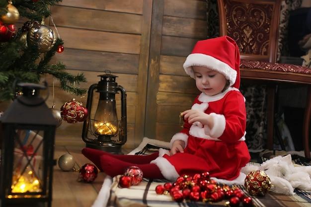 Petit enfant assis devant un arbre de noël et jouant avec des jouets
