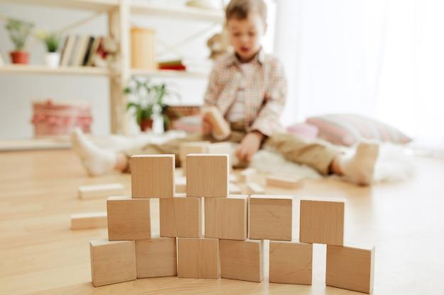 Petit enfant assis par terre. joli garçon jouant avec des cubes en bois à la maison.