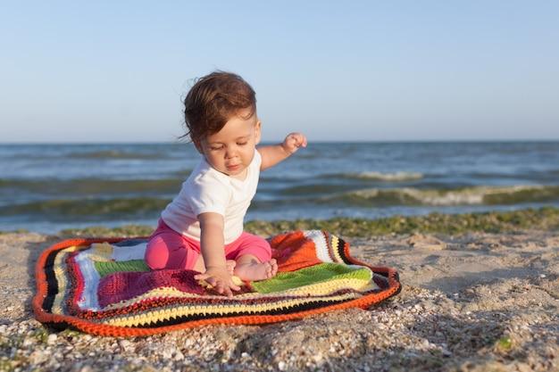 Petit enfant assis sur un tapis coloré au bord de la mer joyeux et heureux