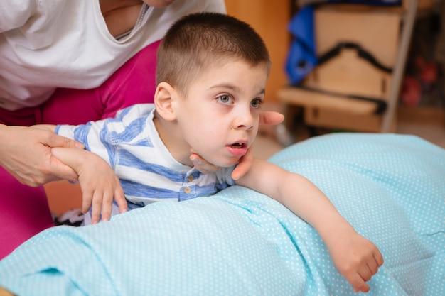Un petit enfant atteint de paralysie cérébrale suit un traitement musculo-squelettique en faisant des exercices