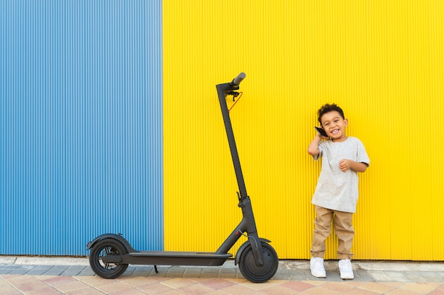 Petit enfant ayant un appel téléphonique à côté d'un scooter.