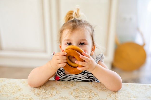Petit enfant bambin en train de déjeuner dans la cuisine chaude et ensoleillée. jeune fille blonde avec une queue de cheval drôle jouant avec deux délicieux bagels