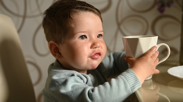 Petit enfant boit de l'eau dans une tasse seul. bébé indépendant