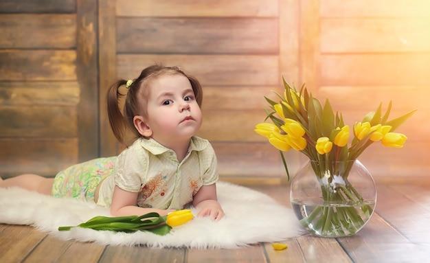Un petit enfant avec un bouquet de tulipes jaunes. un garçon avec un cadeau de fleurs dans un vase. un cadeau pour les filles en vacances avec des tulipes jaunes sur le sol.