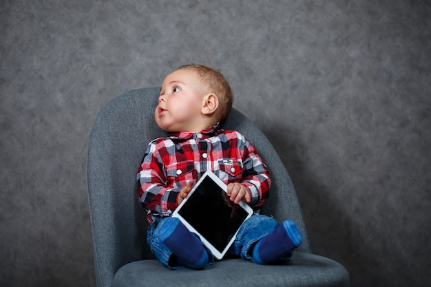 Un petit enfant en chemise joue avec une tablette