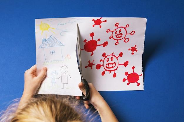 Un petit enfant coupe une partie d'un dessin avec un concept de virus dessiné avec des ciseaux sur la protection de la famille contre le coronavirus
