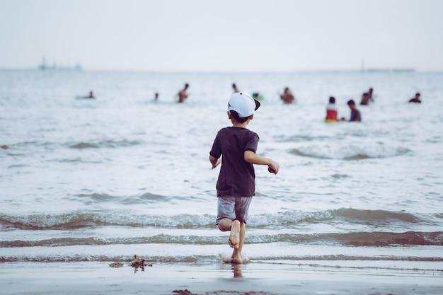 Petit enfant courir à une plage de sable