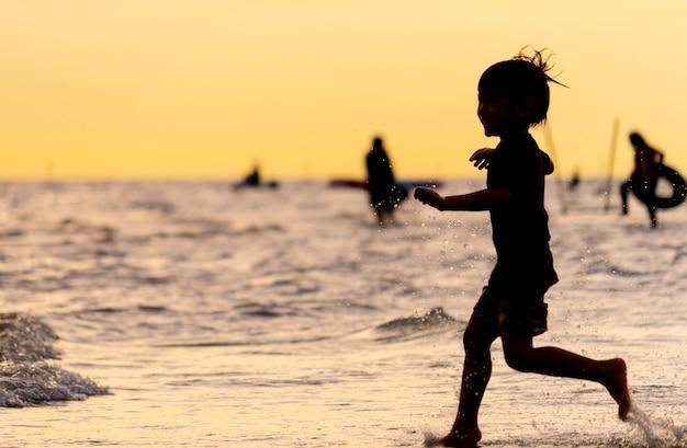 Petit enfant en cours d'exécution sur une silhouette de plage de sable