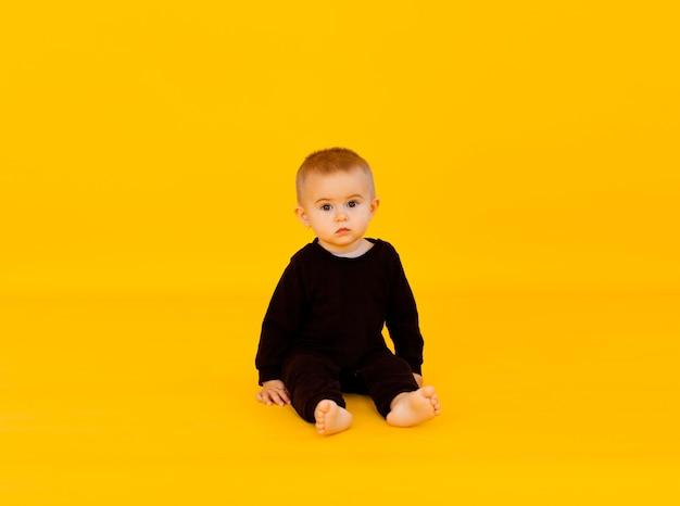 Petit enfant dans un body noir. il sourit, sur fond de studio jaune. articles sur l'enfance, publicité pour les bébés. espace de copie, gros plan
