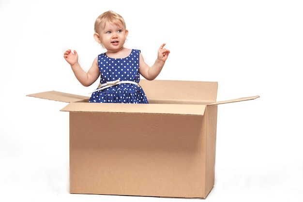 Un petit enfant dans des boîtes en carton sur une surface blanche