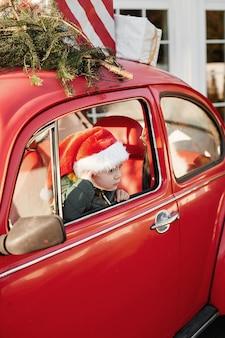 Un petit enfant dans un bonnet de noel est assis dans une voiture d'époque avec un sapin sur le toit pour la période de noël