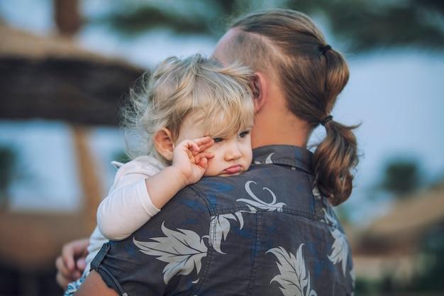 Petit enfant dans les bras du père embrassant le portrait sentimental