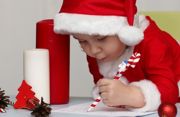 Petit enfant dans un costume du père noël écrivant une lettre avec des voeux pour la nouvelle année