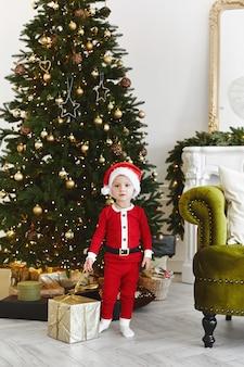 Un petit enfant dans un costume de père noël posant avec une boîte-cadeau de noël près de l'arbre de noël